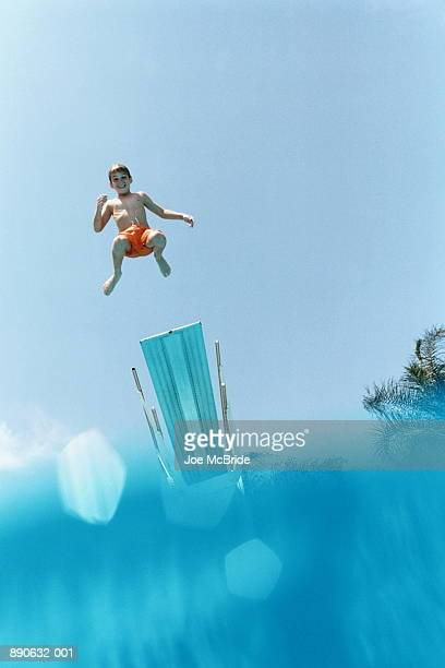 Young swimmer (8-10) jumping into pool