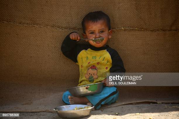 TOPSHOT A young Syrian boy displaced from Raqa eats at the alKaramah camp some 20 kilometres east of the Islamic State group's Syrian bastion on June...