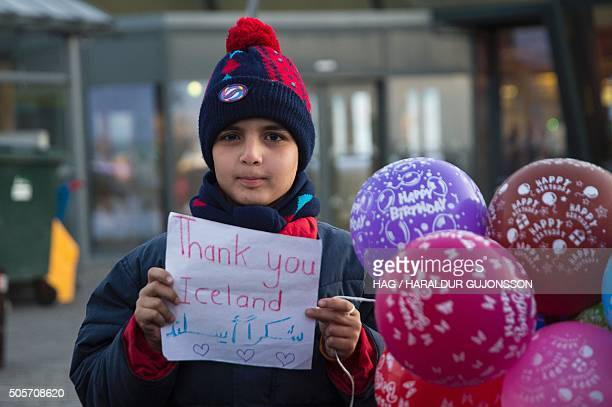 A young Syrian boy holds a sign reading Thank you Iceland as the first group of Syrian refugees arrive on January 19 2016 at Keflavik airport some 50...