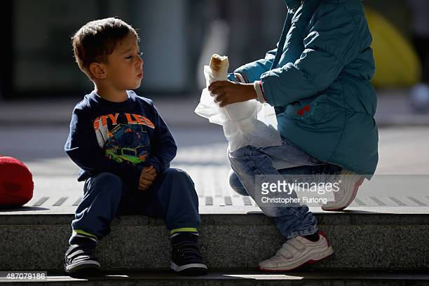 A young Syrian boy is offered food by another child as migrants wait to board a train at Keleti station in central Budapest to take them to the...