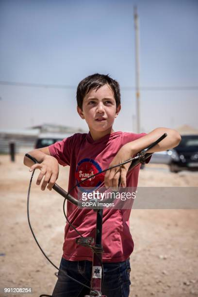 A young Syrian boy stands with his bike in Zaatari refugee camp There are about 14 million Syrian refugees in Jordan and only 20 percent are living...