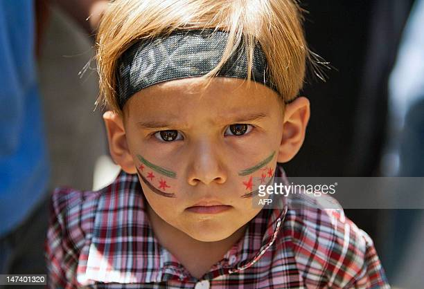 A young Syrian boy with the Syrian reolutionary flag painted on his cheeks stares at the camera during an antigovernment demonstration after Friday...
