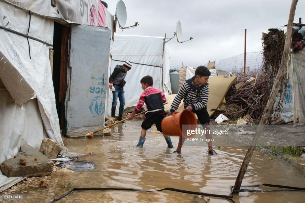 Young Syrian boys help clear out their flooded tent in a... : News Photo