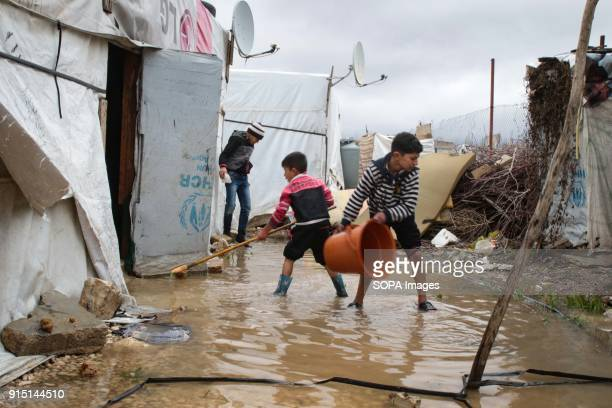 Young Syrian boys help clear out their flooded tent in a refugee camp in Lebanon's Bekaa Valley Lebanon Winter storms create huge challenges for...