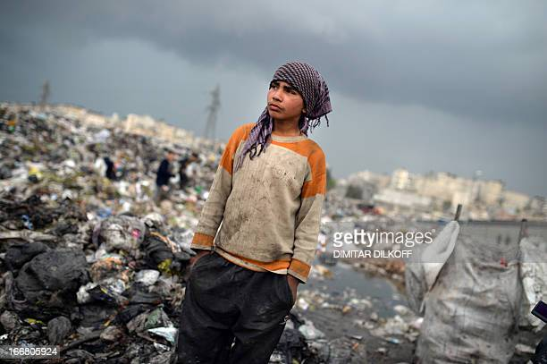 A young Syrian boys takes a rest after collecting plastic and metal items in a garbage dump in the northern Syrian city of Aleppo on April 17 2013...