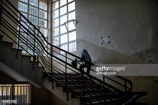 TOPSHOT A young Syrian girl climbs the stairs in an abandoned school used by volunteers for hosting families of refugeees from Syria and Afghanistan...