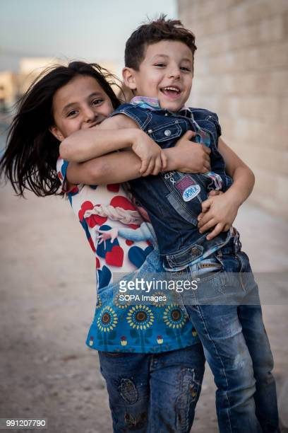 A young Syrian girl holds her brother in a street in Zaatari There are about 14 million Syrian refugees in Jordan and only 20 percent are living in...
