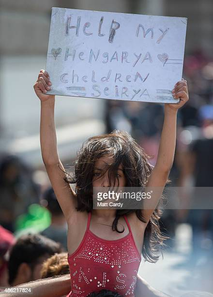 A young Syrian girl holds up a sign as migrants protest outside Keleti station which remains closed to them in central Budapest on September 2 2015...