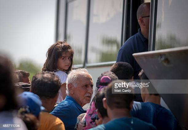 A young Syrian girl is carried on her father's shoulders as migrants who have just crossed the border from Serbia into Hungary queue to board a bus...