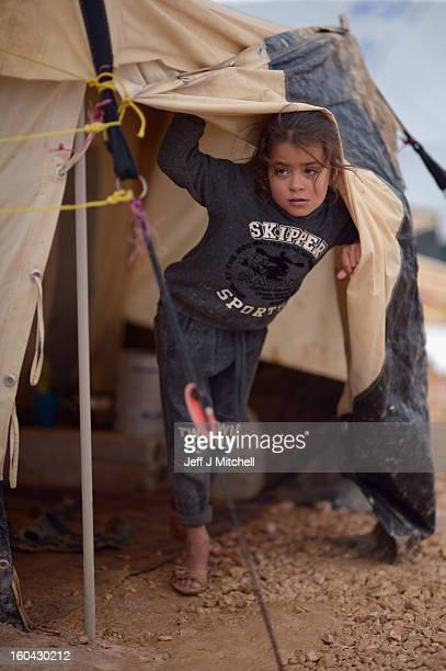 ZA'ATARI JORDAN JANUARY 31 A young Syrian girl looks out from a tent in the Za'atari refugee camp on January 31 2013 in Za'atari Jordan Record...