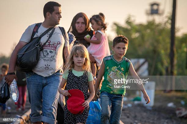 A young Syrian girl walks with her family as migrants cross the border from Serbia into Hungary close to the village of Roszke on August 29 2015 near...
