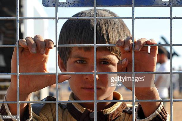 A young Syrian Kurdish refugee enters Turkey at the Yumurtalik crossing gate on September 23 2014 in Turkey As many as 138000 Syrian Kurds have...