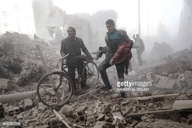 TOPSHOT A young Syrian man carries a wounded child following reported government airstrike on the rebelheld town of Douma on the eastern outskirts of...