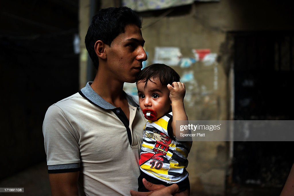 A young Syrian man, who arrived to Lebanon last month, holds his nephew in a poor neighborhood with a high concentration of Syrian refugees on June 30, 2013 in Beirut, Lebanon. Currently the Lebanese government officially hosts 546,000 Syrians with an estimated additional 500,000 who have not registered with the United Nations. Lebanon, a country of only 4 million people, is now home to the largest number of Syrian refugees who have fled the conflict. The situation is beginning to put a huge social and political strains on Lebanon as there is currently no end in sight to the war in Syria.