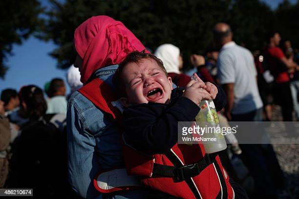 A young Syrian migrant infant cries while being carried by his mother as they wait next to railroad tracks where migrants cross into Macedonia...