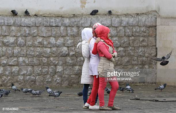 Young Syrian Muslim women walk past the walls of Damascus' landmark Ummayad mosque early on March 14 2016 As the Syrian conflict enters its sixth...