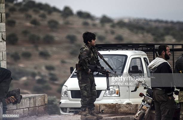 A young Syrian rebel fighter holding a weapon waits on a road in Bab alHawa near the Syrian border with Turkey on December 16 2016 The Syrian...