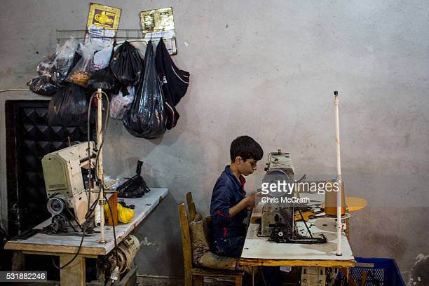 A young Syrian refugee boy makes shoe parts in a Turkish owned factory on May 16 2016 in Gaziantep Turkey Since fleeing the war and after the new EU...