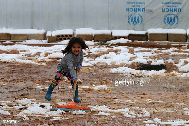 A young Syrian refugee cleans the mud as snow covers the ground outside tents supplied by the United Nations High Commissioner for Refugees for...