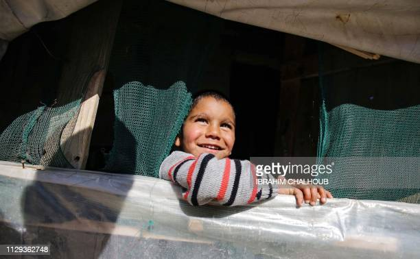 A young Syrian refugee looks on from inside a tent at a refugee camp in the village of Mhammara in the northern Lebanese Akkar region on March 9 2019