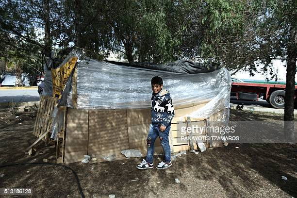 A young Syrian refugee stands outside his family's makeshift shelter at the port of Piraeus on March 1 2016 More than 131000 migrants and refugees...