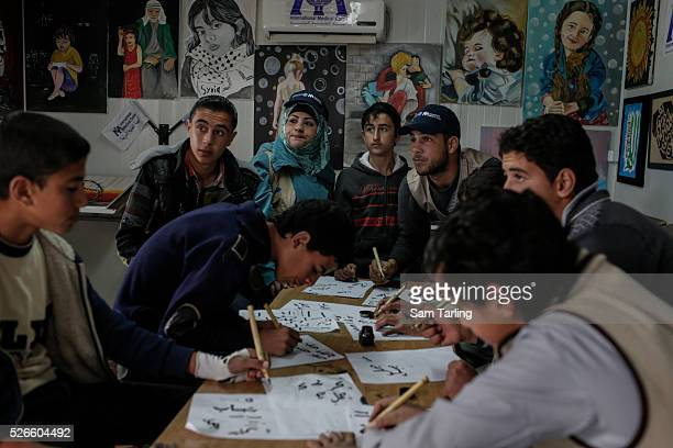 Young Syrian refugees learn calligraphy as they wait for Prince Charles to visit a 'Child Friendly Space' at Zaatari Syrian refugee camp on February...