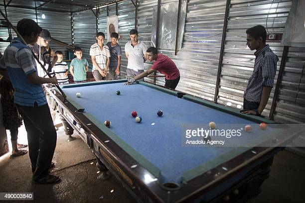 Young Syrian refugees play billiards at a prefabricated billiards saloon at a tent city in the Akcakale District of Sanliurfa Turkey on September 24...