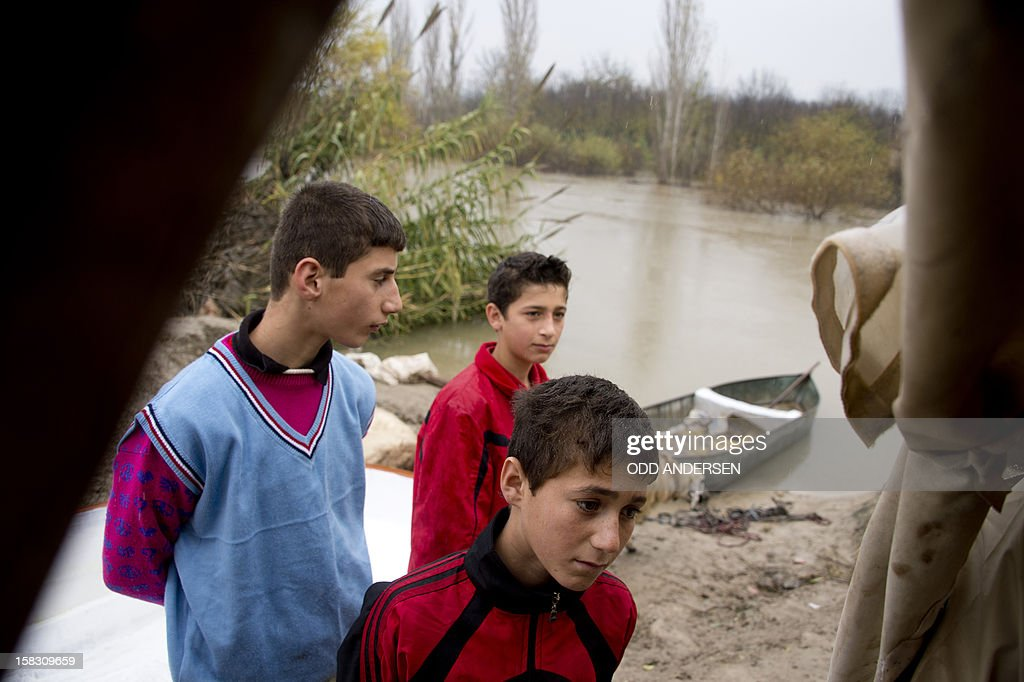 Young Syrian refugees stand outside a tent after arriving to the Turkish side of the Orontes river after fleeing from the northern Syrian town of Darkush on December 13, 2012. The number of Syrian refugees registered in neighbouring countries and North Africa has passed half a million, the UN's refugee body said, adding that many more have not come forward to seek help.