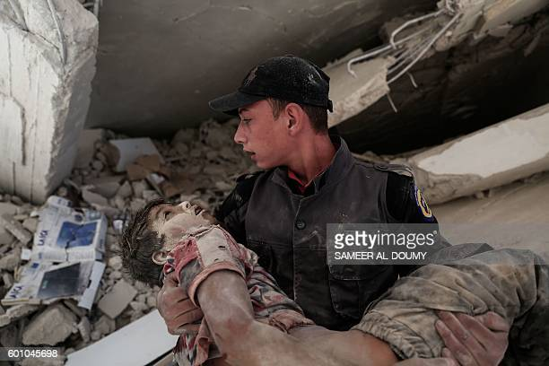 TOPSHOT A young Syrian rescue worker carries a wounded boy away from the rubble of a building following reported air strikes on the rebelheld town of...