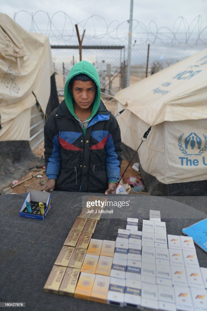 ZA'ATARI, JORDAN - JANUARY 31: A young Syrian sells cigarettes in the Za'atari refugee camp on January 31, 2013 in Za'atari, Jordan. Record numbers of refugees are fleeing the violence and bombings in Syria to cross the borders to safety in northern Jordan and overwhelming the Za'atari camp. The Jordanian government are appealing for help with the influx of refugees as they struggle to cope with the sheer numbers arriving in the country.