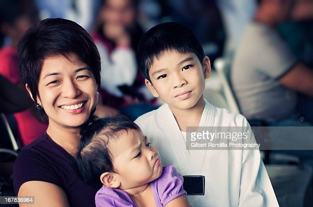 young taekwondo fighter with mother and sister - malabon stock pictures, royalty-free photos & images