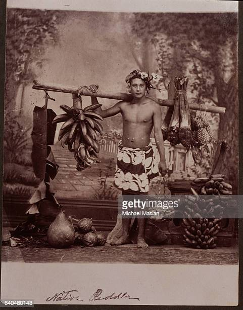 A young Tahitian man a fruit peddler holds a stick laden with fruit over one shoulder He is wearing a printed piece of cloth around his waist and has...