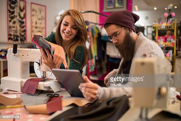 Jeune tailleurs coopération tout en travaillant sur tablette numérique.