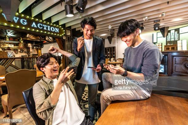 young taiwanese adults playing mobile game at a coffee shop / bar - leisure games ストックフォトと画像