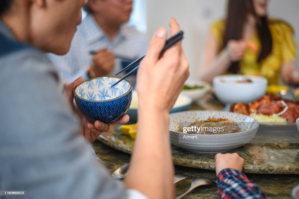 Young Taiwanese Couple Enjoying Lunch at Home with Family : Stock Photo