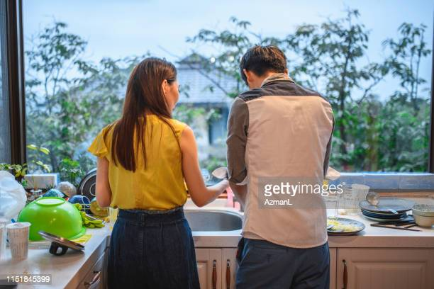 young taiwanese couple washing dishes together after lunch - couples showering stock pictures, royalty-free photos & images