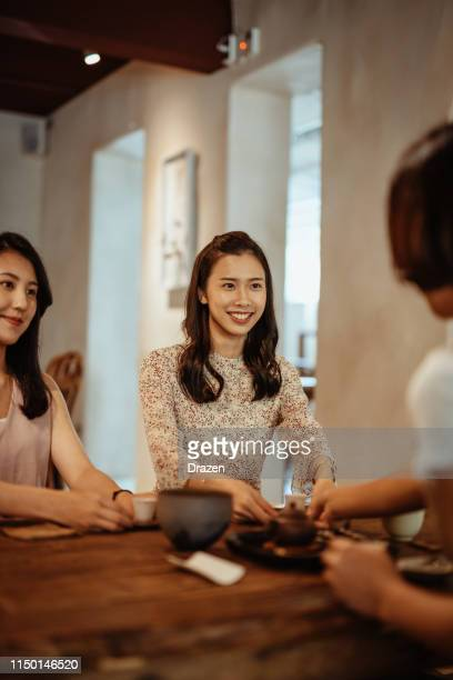 Young Taiwanese women enjoy idyllic atmosphere in traditional tea house.