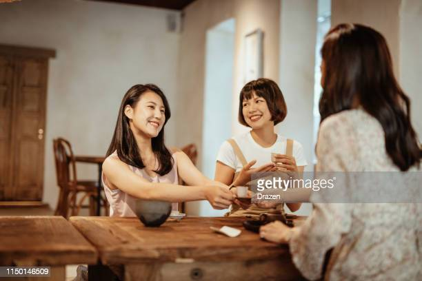 Young Taiwanese women sharing secrets during coffee and tea break.