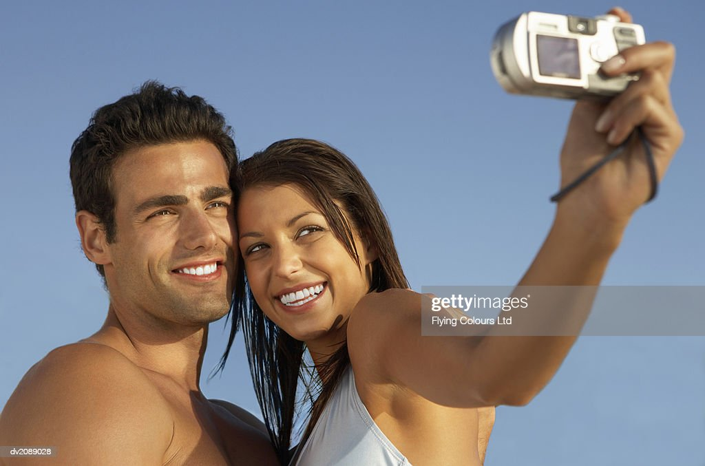 Young Tanned Couple Take a Photograph of Themselves With a Digital Camera : Stock Photo