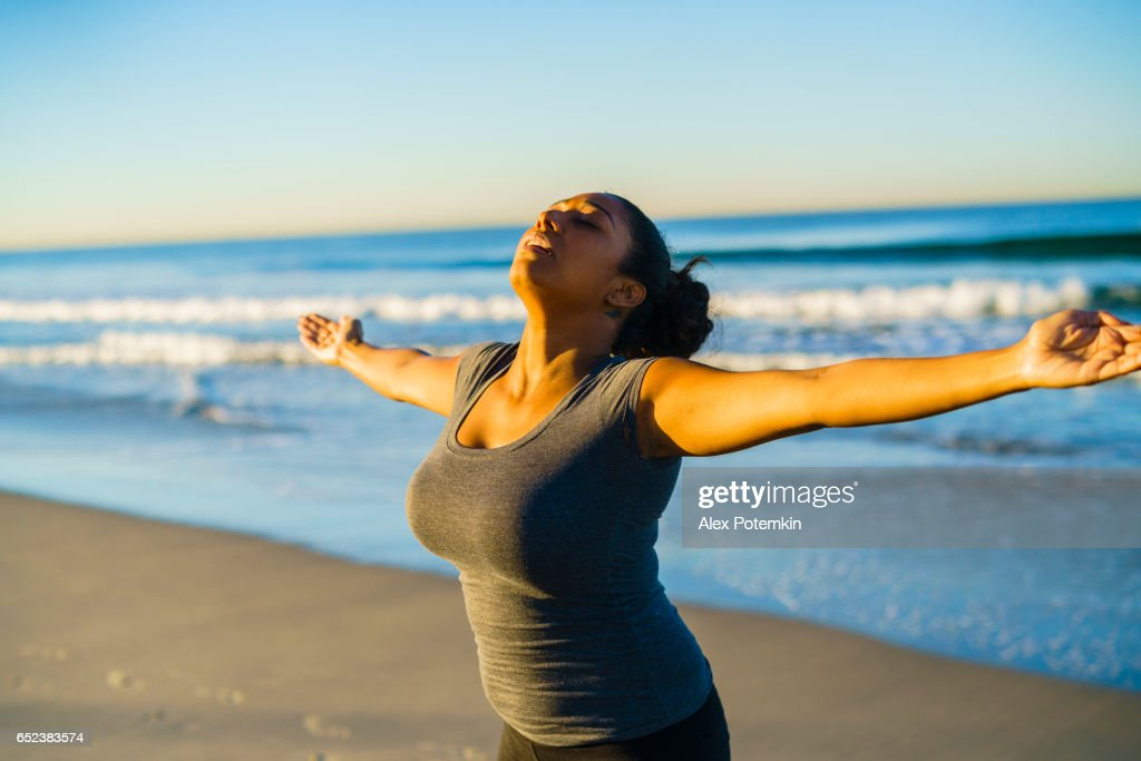 Young tanned mixed-race girl practicing fitness on the beach : Stock Photo