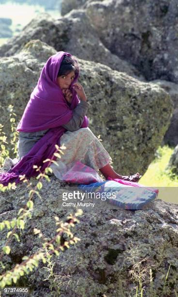 Young Tarahumara girl sits on a rock, Copper Canyon, Mexico, 1998.