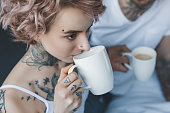 young tattooed girl drinking coffee at morning, boyfriend sitting behind