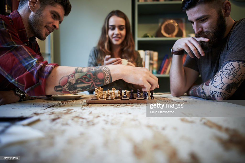 Young tattooed males playing chess : Stock Photo