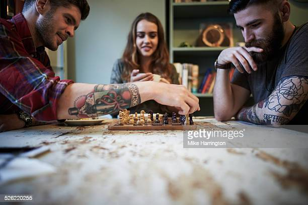 Young tattooed males playing chess