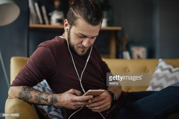 Getatoeëerde jongeman is ontspannen op de sofa en luistert naar de podcast