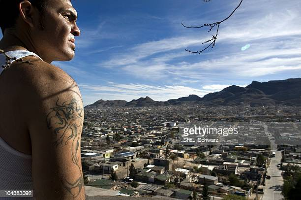 Young tattooed man stands on the hill overlooking the city of JuarezThe death industry is booming in the city of Juarez Since Mexican President...