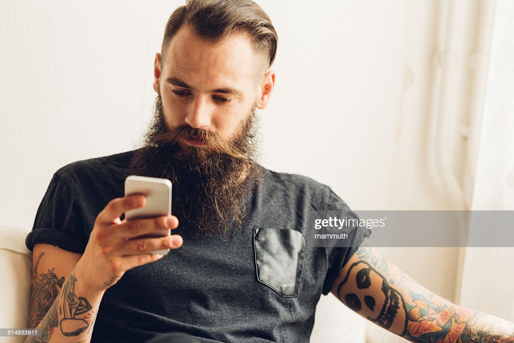 young tattooed man using mobile phone : Stock Photo
