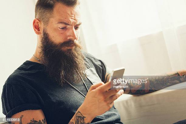 young tattooed man using mobile phone