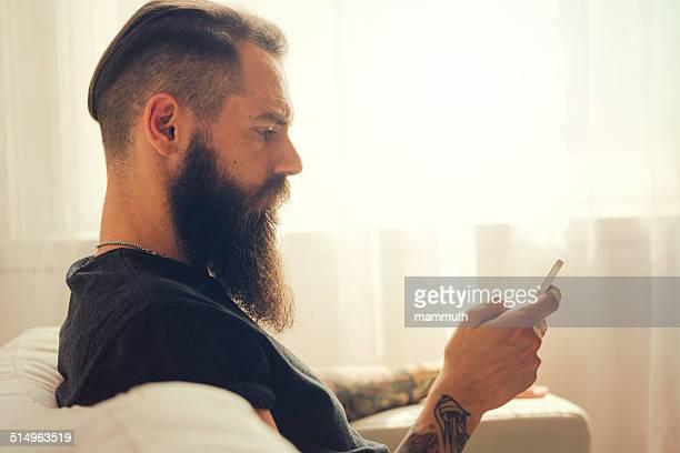 tattooed 若い男の携帯電話を使用する