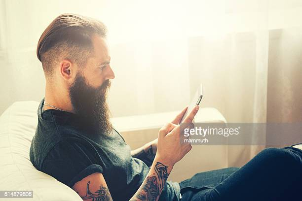 young tattooed man using tablet